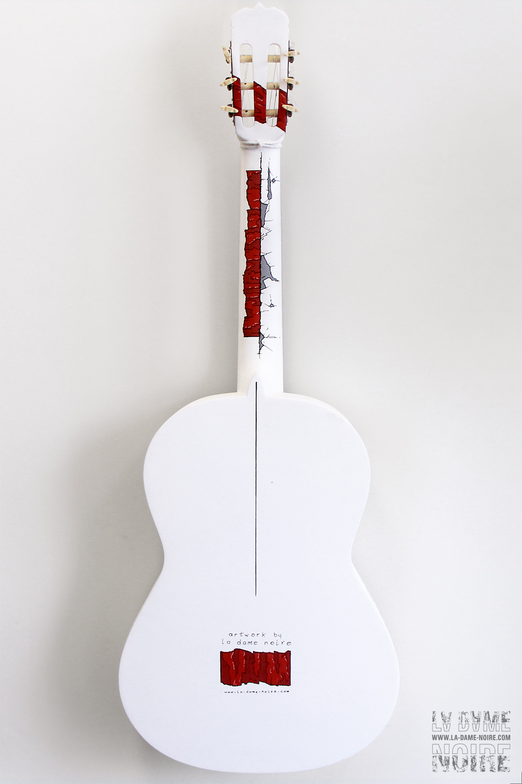Back side side of an acoustic guitar painted in white and red