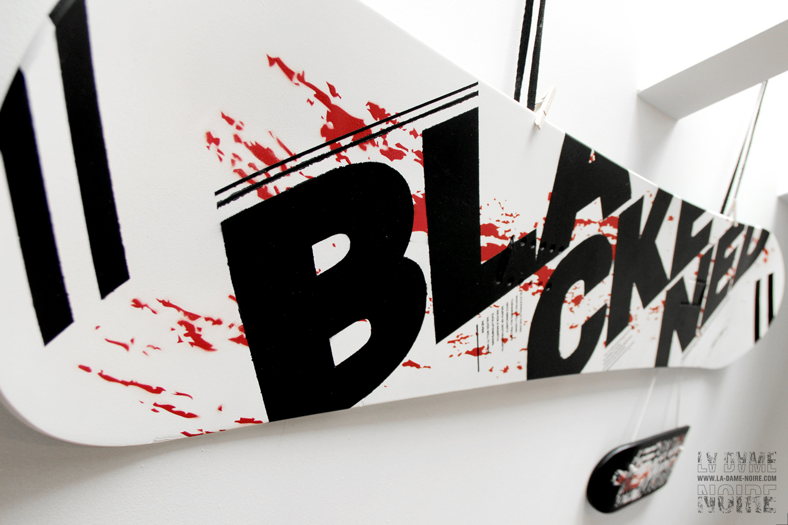 Snowboard painted in black, white, red, and the word Blackened in big bold letters