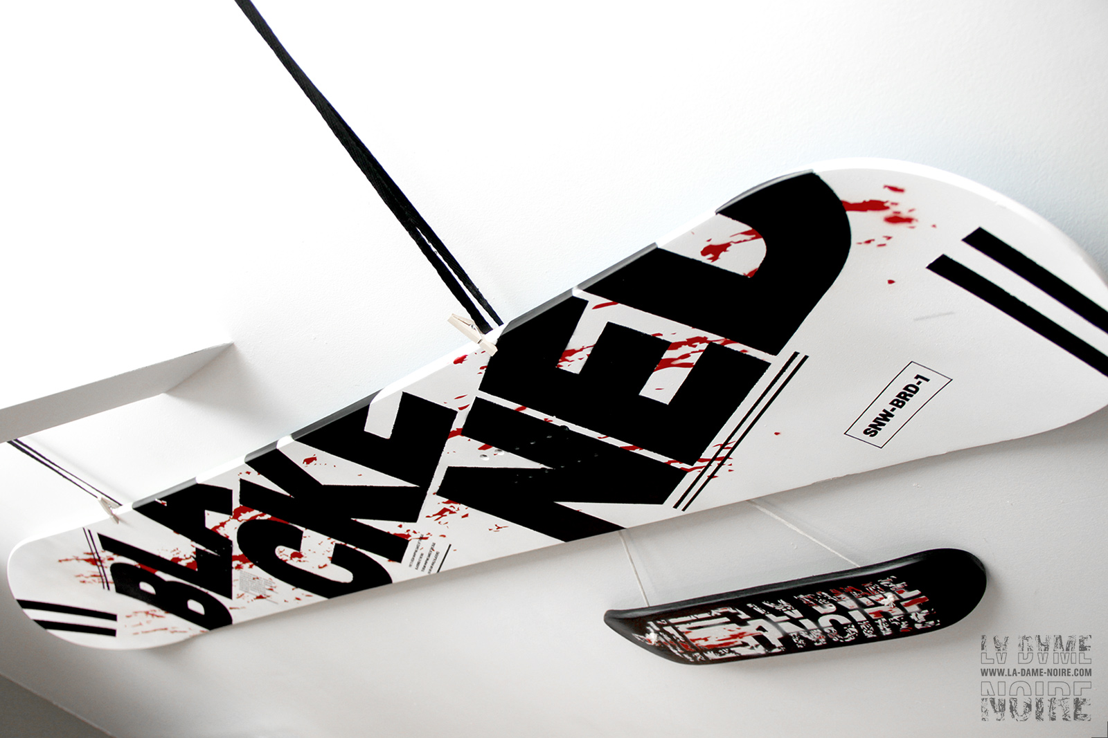 Details of the snowboard painted in black, white, red, and the word Blackened in big bold letters